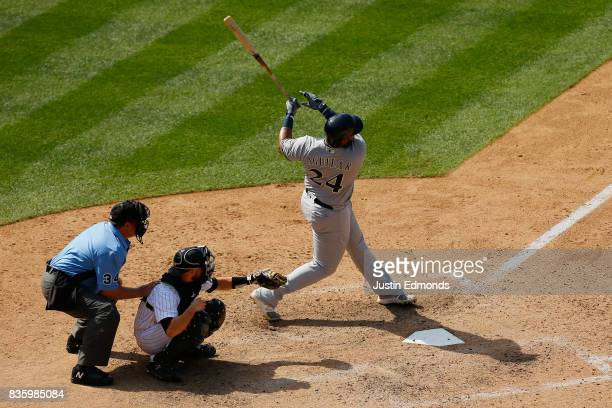 Jesus Aguilar of the Milwaukee Brewers follows through on a tworun home run as catcher Jonathan Lucroy of the Colorado Rockies and home plate umpire...