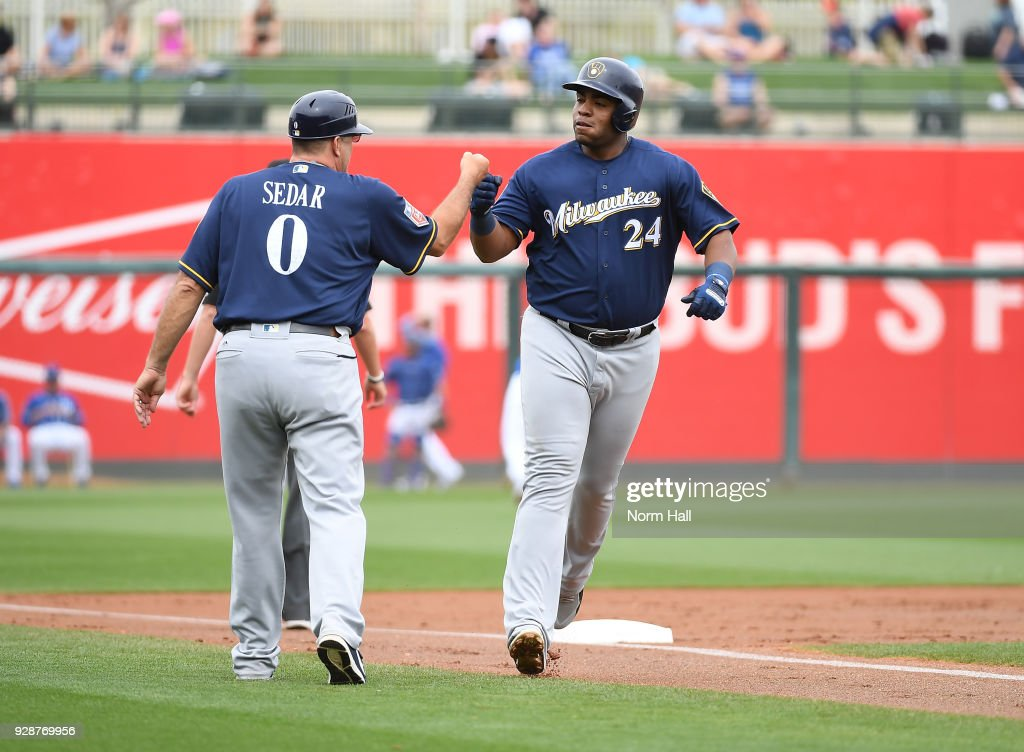 Jesus Aguilar #24 of the Milwaukee Brewers is congratulated by third base coach Ed Sedar #6 after hitting a solo home run against the Kansas City Royals during the second inning of a spring training game at Surprise Stadium on March 7, 2018 in Surprise, Arizona.