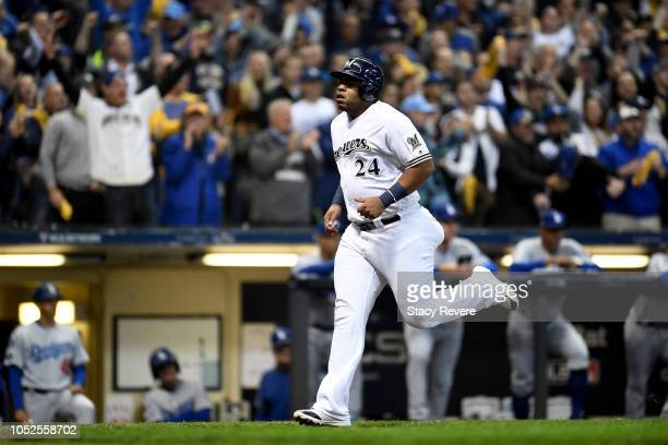 Jesus Aguilar of the Milwaukee Brewers scores a run against the Los Angeles Dodgers during the first inning in Game Six of the National League...