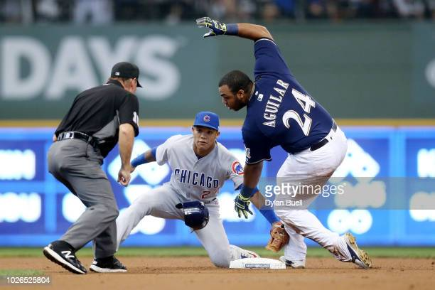 Jesus Aguilar of the Milwaukee Brewers slides into second base for a double past Addison Russell of the Chicago Cubs in the first inning at Miller...
