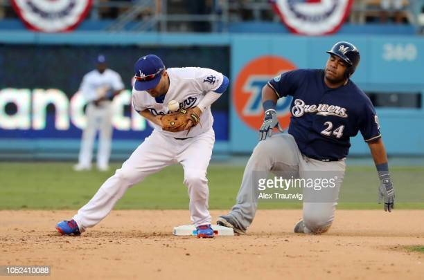 Jesus Aguilar of the Milwaukee Brewers slides safely into second as Brian Dozier of the Los Angeles Dodgers can't make the play in the ninth inning...