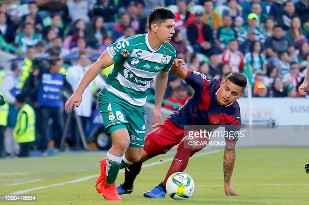 Jesus Angulo of Santos vies for the ball with Alexis Vega of Guadalajara during their Mexican Clausura 2019 tournament football match at the TSM...