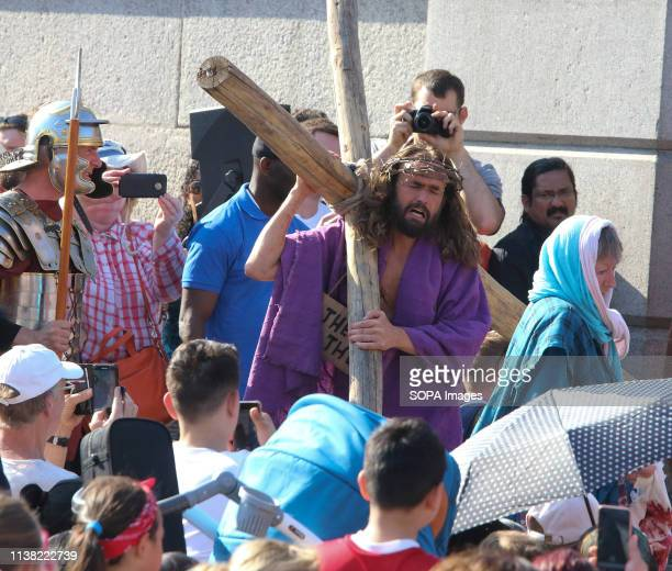 Jesus Christ carries his own cross during a performance of 'The Passion of Jesus' by Wintershall players in Trafalgar Square Around 20000 people...