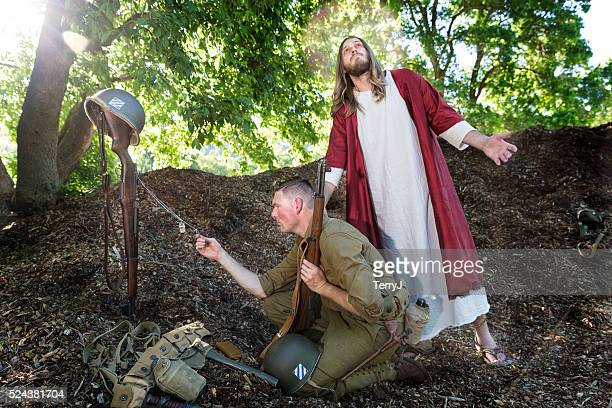 jesus christ look up while a soldier prays - dead soldier stock photos and pictures