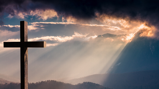 Jesus Christ wooden cross on a dramatic, colorful sunset 612253604