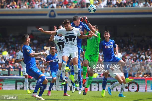 Jesus Corona and Pablo Aguilar of Cruz Azul struggles for the ball with Nicolas Freire of Pumas during the 10th round match between Pumas UNAM and...