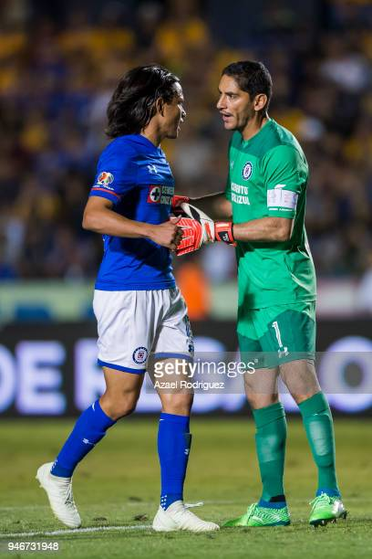 Jesus Corona goalkeeper of Cruz Azul talks to Gerardo Flores as he leaves the field after receiving a red card during the 15th round match between...