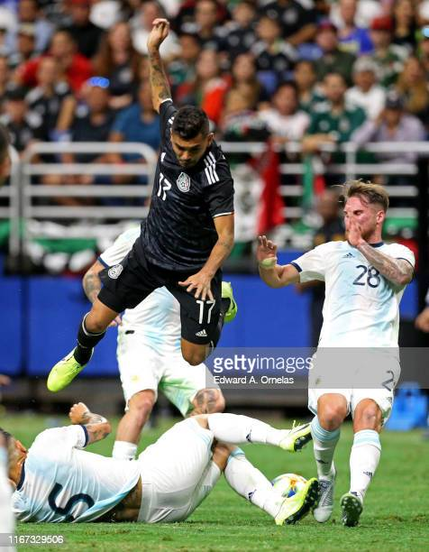 Jesus Corona of Mexico leaps over Leandro Paredes of Argentina as Alexis Mac Allister of Argentina moves in on the play during the International...