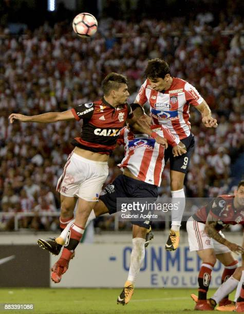 Jesus David Murillo and Roberto Ovelar of Junior jump for the ball with Lucas Paqueta of Flamengo during a second leg match between Junior and...