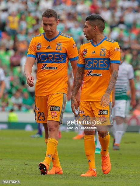 Jesus Dueñas and Javier Aquino of Tigres leave the field after the quarter finals second leg match between Santos Laguna and Tigres UANL as part of...