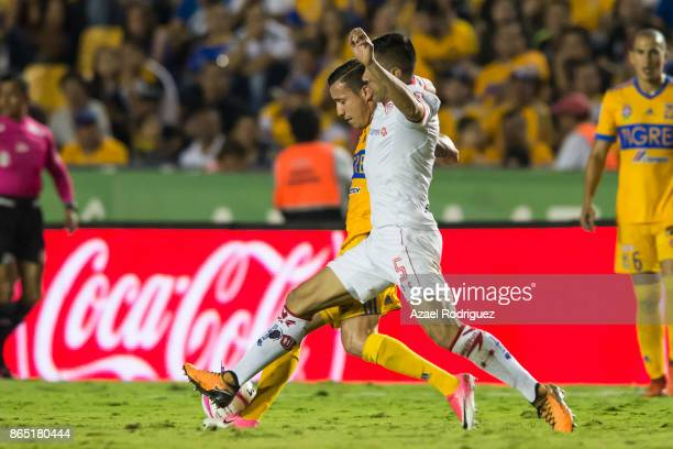 Jesus Dueñas of Tigres fights for the ball with Osvaldo Gonzalez of Toluca during the 14th round match between Tigres UANL and Toluca as part of the...