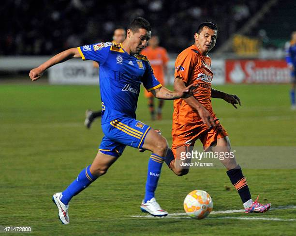 Jesuœs Due–ñas of Tigres struggles for the ball with Jorge Flores of Universiario Sucre during a first leg match between Universitario Sucre and...