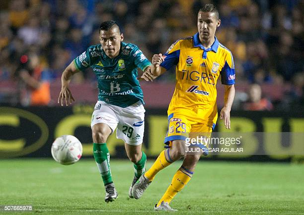Jesus Dueñas of Tigres vies for the ball with Aldo Rocha of León during the Mexican Clausura 2016 tournament football match at the Universitario...
