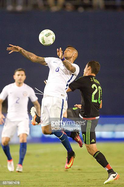 Jesus Duenas of Mexico vies for the ball with Arturo Vidal of Chile during the friendly match between the Mexican national team and Chile national...