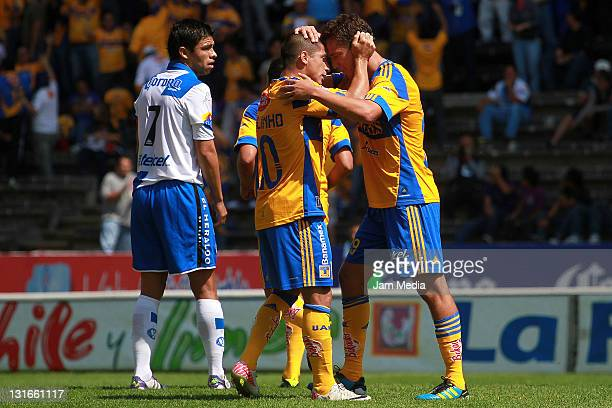 Jesus Duenas of Tigres celebrates with teammates a scored goal against Puebla during a match as part of the Apertura 2011 at Cuauhtemoc Stadium on...
