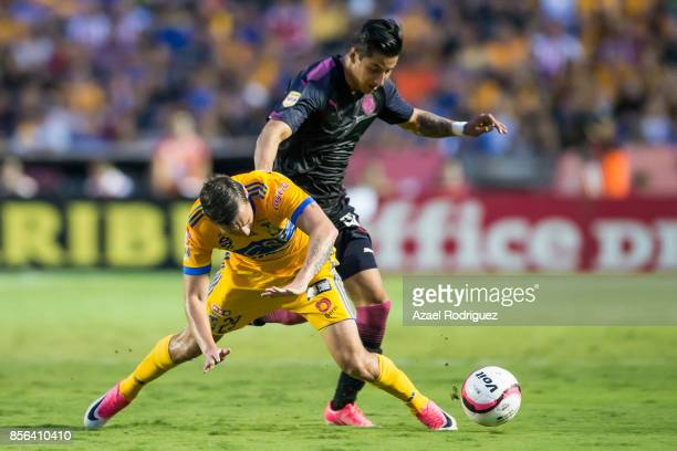 Jesus Duenas of Tigres fights for the ball with Carlos Cisneros of Chivas during the 12th round match between Tigres UANL and Chivas as part of the...