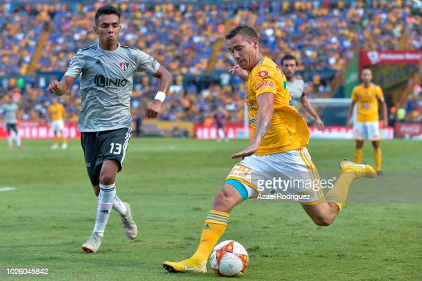 Jesus Duenas of Tigres kicks the ball while observed by Ulises Cardona of Atlas during the 6th round match between Tigres UANL and Veracruz as part...