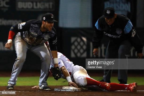 Jesus Fabela of Diablos Rojos is tagged out on third base by Alex Liddi of Toros de Tijuana during the match between Toros de Tijuana and Diablos...