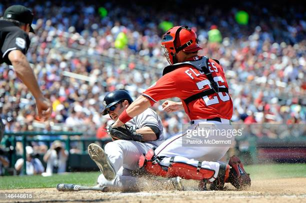 Jesus Flores of the Washington Nationals tags Nick Swisher of the New York Yankees out at home plate in the sixth inning during a game at Nationals...