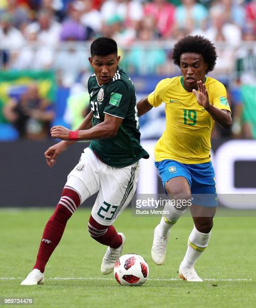 Jesus Gallardo of Mexico is challenged by Willian of Brazil during the 2018 FIFA World Cup Russia Round of 16 match between Brazil and Mexico at...