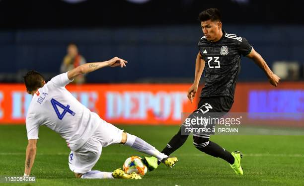 Jesus Gallardo of Mexico vies for the ball with Mauricio Isla of Chile during the international friendly match between Mexico and Chile at SDCCU...