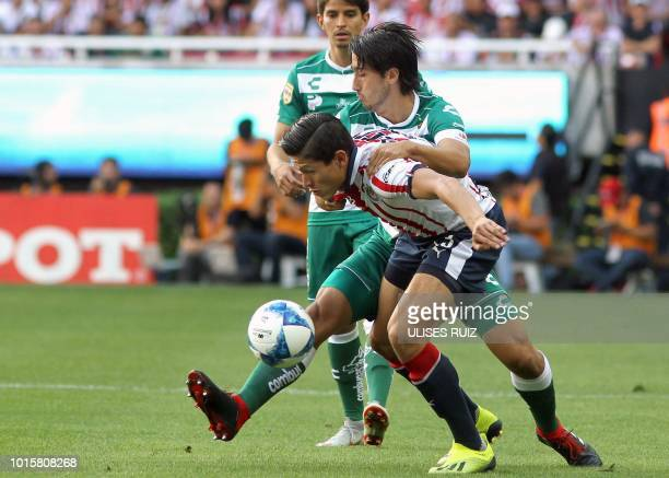 Jesus Godinez of Guadalajara vies for the ball with Javier Abella of Santos during their Mexican Apertura 2018 tournament football match at Akron...