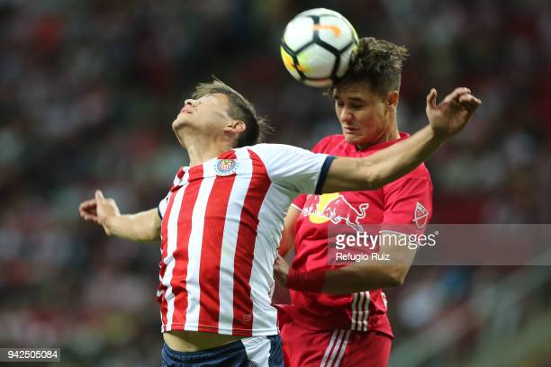 Jesus Godínez of Chivas jumps for the ball with Alex Muyl of New York RB during the semifinal match between Chivas and New York RB as part of the...