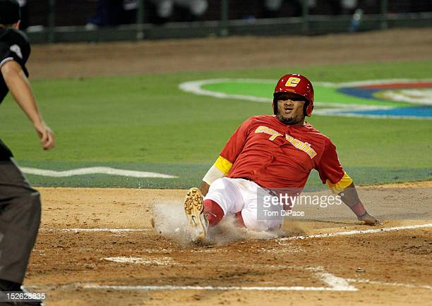 Jesus Golindano of Team Spain slides into home plate to score a run against Team France during game 2 of the Qualifying Round of the 2013 World...