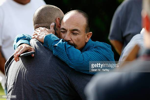 Jesus Gonzalez and Pastor Ernie Ceballos hug outside the crime scene where the suspects of the Inland Resource Center were killed on December 3, 2015...
