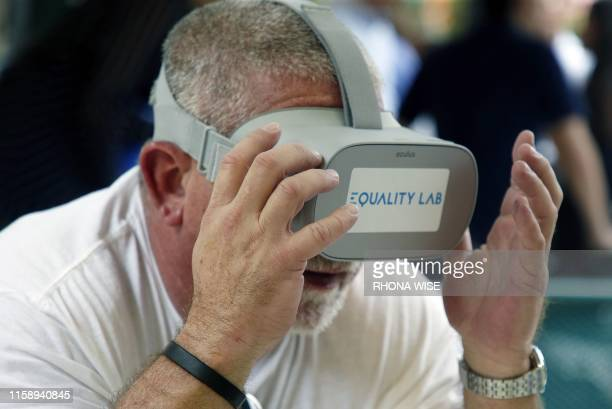 Jesus Gonzalez samples a virtual reality experience in the Little Havana neighborhood of Miami, Florida on July 26, 2019. French born scientist,...