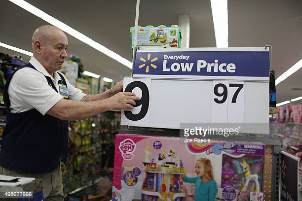 Jesus Gutierrez puts a low price dollar sign together at a Walmart store as they prepare for Black Friday shoppers on November 24 2015 in Miami...