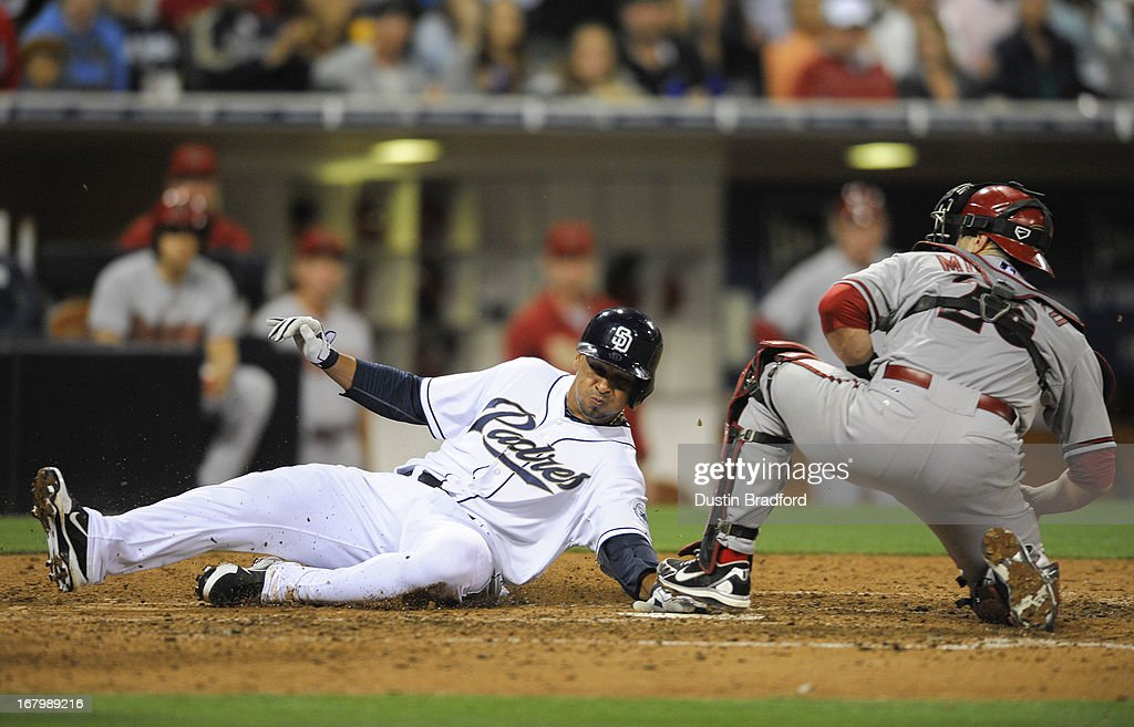 Jesus Guzman #15 of the San Diego Padres scores ahead of the tag of Miguel Montero #26 of the Arizona Diamondbacks during the seventh inning of a baseball game at Petco Park on May 3, 2013 in San Diego, California.