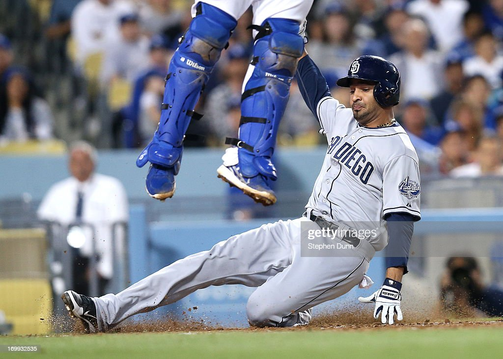 Jesus Guzman #15 of the San Diego Padres slides under catcher Tim Federowicz #18 of the Los Angeles Dodgers to score a run as Federowicz jumps for a high throw in the fourth inning at Dodger Stadium on June 4, 2013 in Los Angeles, California.