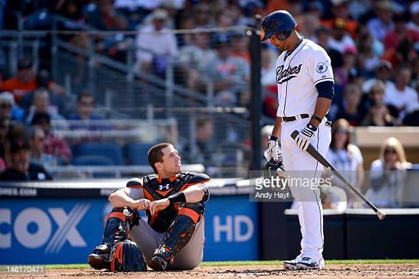 Jesus Guzman of the San Diego Padres talks to Buster Posey of the San Francisco Giants after Posey was hit with a foul tip at Petco Park on June 6...