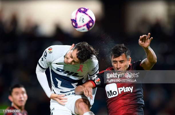 Jesus Isijara of Atlas heads the ball with Alan Mozo of Pumas during their Mexican Apertura tournament football match at the Olimpico 68 stadium on...