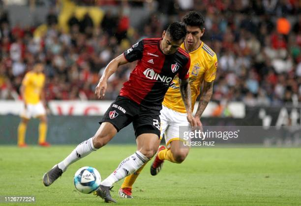 Jesus Isijara of Atlas vies for the ball with Francisco Venegas of Tigres during the Mexican Clausura 2018 tournament football match between Tigres...
