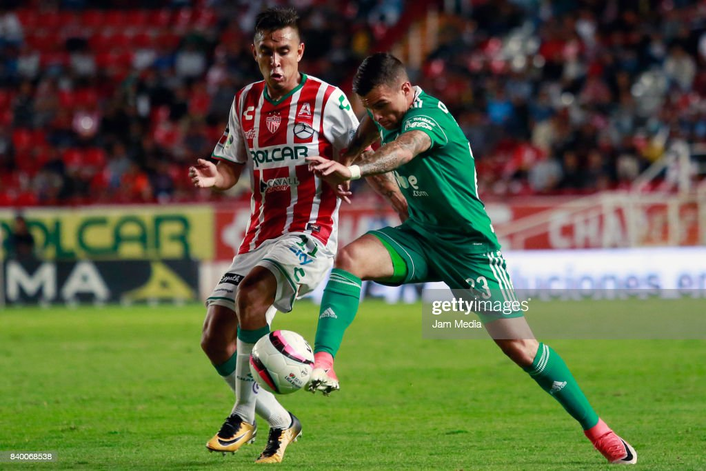 Jesus Isijara (L) of Necaxa and Christian Tabo (R) of Atlas fight for the ball during the seventh round match between Necaxa and Atlas as part of the Torneo Apertura 2017 Liga MX at Victoria Stadium on August 26, 2017 in Aguascalientes, Mexico.