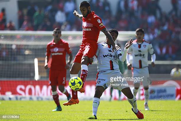 Jesus Mendez of Toluca struggles for the ball with Luis Robles of Atlas during the 1st round match between Toluca and Atlas as part of the Torneo...