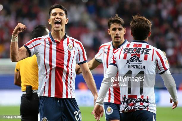 Jesus Molina of Chivas celebrates with teammates after scoring the first goal of his team during the first round match between Chivas and Tijuana as...