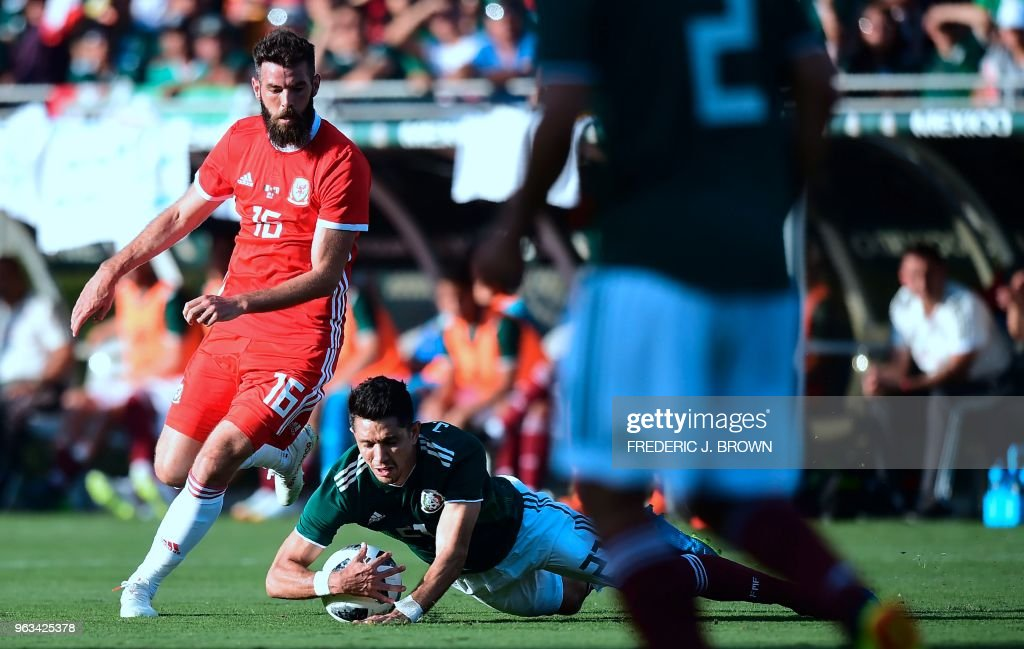 Jesus Molina of Mexico (C/on ground) vies for the ball with Joe Ledley of Wales (L/#16) during their international soccer friendly at the Rose Bowl in PAsadena, California on May 28, 2018.