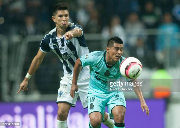 Jesus Molina of Monterrey vies for the ball with Osvaldo Martinez of Santos during the Mexican Apertura 2017 tournament football match at the BBVA...