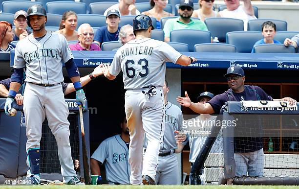 Jesus Montero of the Seattle Mariners celebrates after scoring a fifth inning run against the New York Yankees with teammate Robinson Cano and...