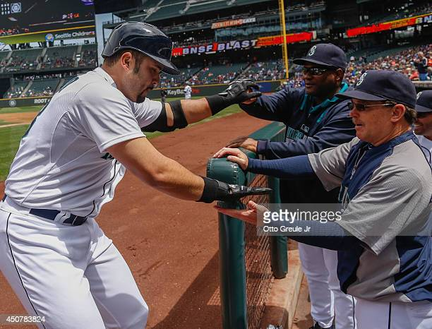 Jesus Montero of the Seattle Mariners is congratulated by manager Lloyd McClendon and hitting coach Howard Johnson after hitting a tworun home run in...