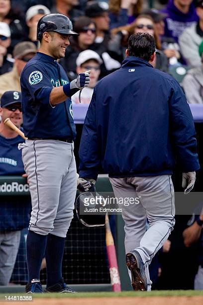 Jesus Montero of the Seattle Mariners shares a laugh with starting pitcher Jason Vargas after Vargas scored during a game against the Colorado...