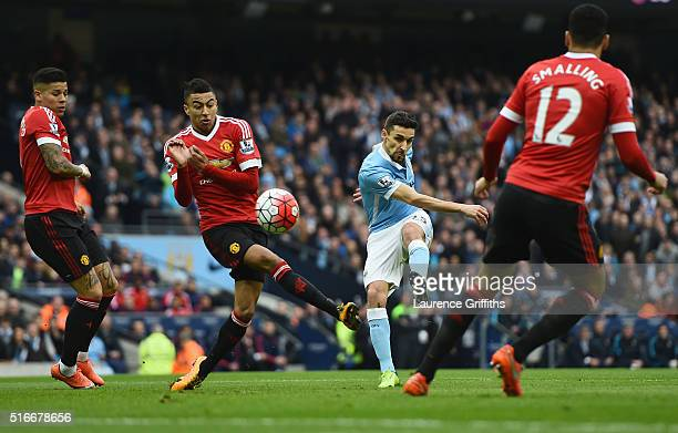 Jesus Navas of Manchester City shoots past Marcos Rojo and Jesse Lingard of Manchester United during the Barclays Premier League match between...