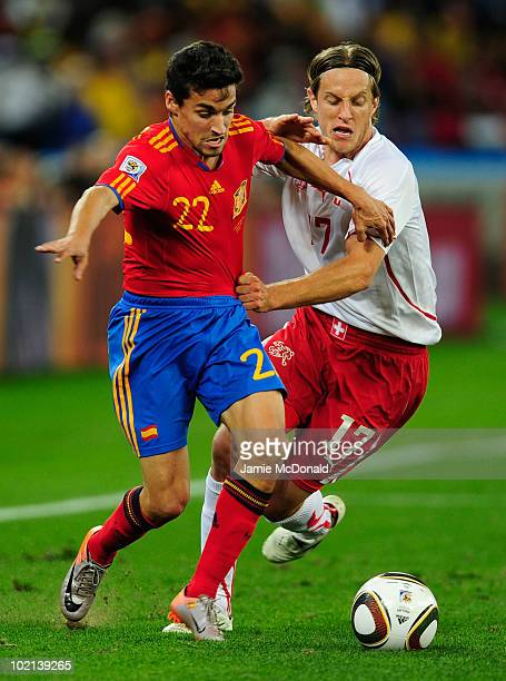 Jesus Navas of Spain is held back by Reto Ziegler of Switzerland during the 2010 FIFA World Cup South Africa Group H match between Spain and...
