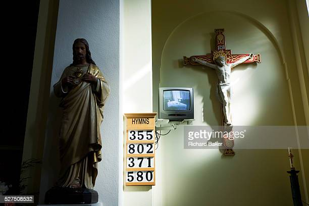 Jesus on the cross with TV screen inside at St Lawrence's Catholic church in Feltham London On the walls of this 1930s church transept we see a...