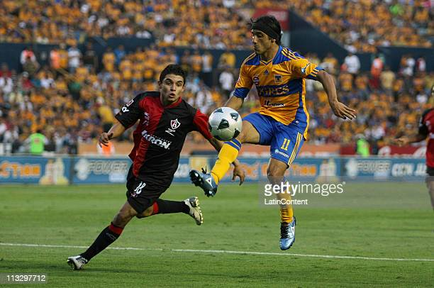 Jesus Paganoni of Atlas struggles for the ball with Damian Alvarez of Tigres during the Clausura 2011 Tournament in the Mexican Football League at...
