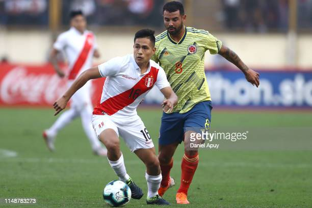 Jesus Pretell of Peru and Edwin Cardona of Colombia compete for the ball during a friendly match between Peru and Colombia at Estadio Monumental on...