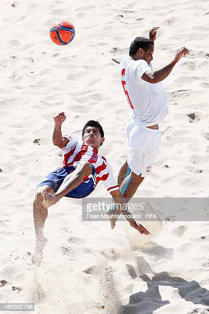 Jesus Rolon of Paraguay attempts a scissor kick shot on goal in front of Raimoana Bennett of Tahiti during the Group D FIFA Beach Soccer World Cup...
